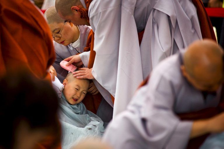 A Buddhist monk shaves the head of a novice monk during an inauguration ceremony at Jogye temple in Seoul, May 11, 2015. Ten children on Monday were given the opportunity to experience life as Buddhist monks by staying at the temple until Buddha's birthday in two weeks.  REUTERS/Thomas Peter  TPX IMAGES OF THE DAY