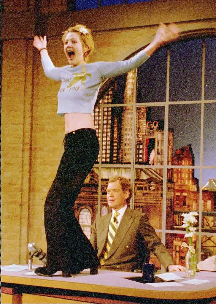 Actress Drew Barrymore dances on the desk of David Letterman during taping of CBS'