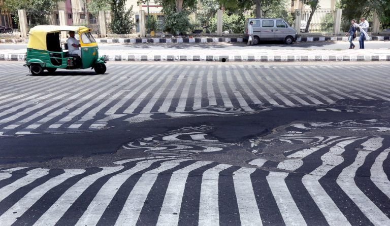 epaselect epa04769715 Road markings appear distorted as the asphalt starts to melt due to the high temperature in New Delhi, India, 27 May 2015. More than 1,150 people are reported dead from a heat wave sweeping across south India and Andhra Pradesh state was the worst hit, where 884 people had died of heatstroke since 18 May. Weather officials said northwesterly dry and hot winds from the desert state of Rajasthan were responsible. EPA/HARISH TYAGI