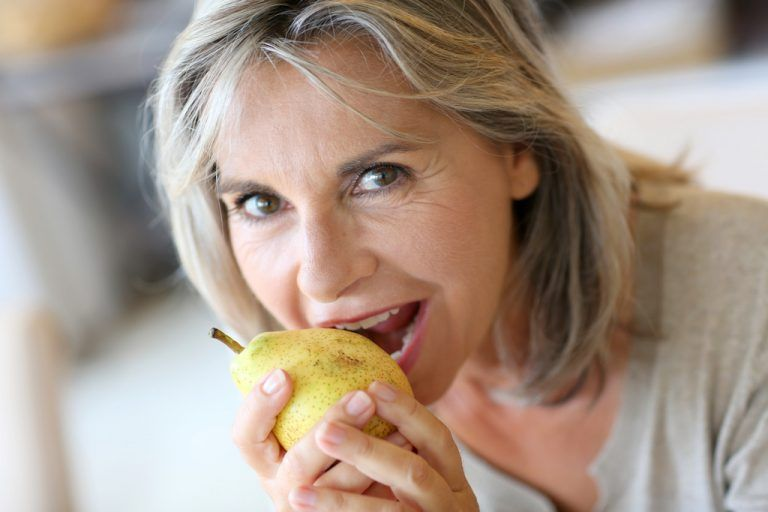 Portrait of senior woman eating pear
