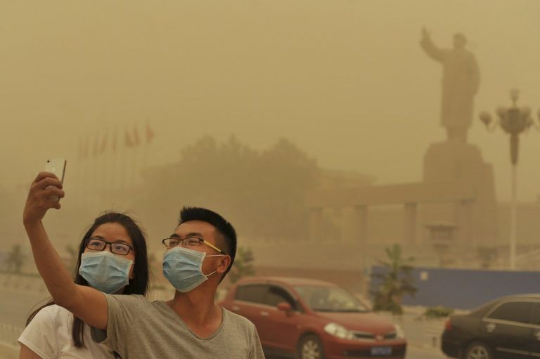 Residents wearing masks pose for a photograph near a statue of late Chinese Chairman Mao Zedong, as a sandstorm hits Kashgar, Xinjiang Uighur Autonomous Region, China, May 10, 2015. Picture taken May 10, 2015. REUTERS/Stringer TPX IMAGES OF THE DAY CHINA OUT. NO COMMERCIAL OR EDITORIAL SALES IN CHINA