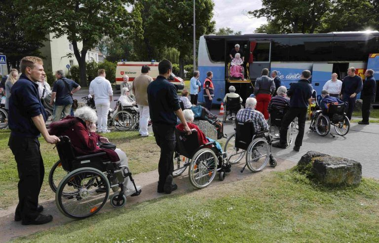 Worker's of Germany's Arbeiter Samariter Bund ASB, a welfare organisation engaged in civil protection, rescue and social services line up handicapped pensioners to evacuated a nearby nursing home in a special bus in Cologne, Germany May 27, 2015. Some 20,000 residents in the western German city of Cologne are being forced to evacuate their homes after authorities discovered a 440-pound bomb dropped during World War Two by the U.S. Air Force. Schools and kindergartens remained closed and dozens of ambulances were on the scene to evacuate residents of a nursing home. REUTERS/Wolfgang Rattay