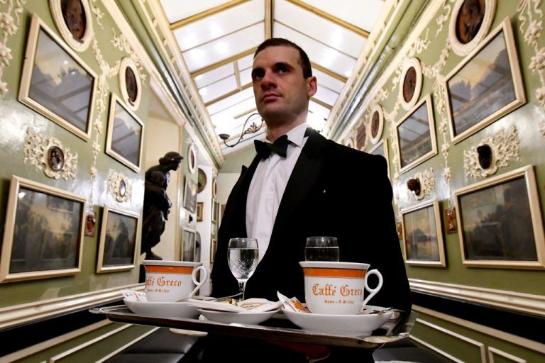 A waiter carries coffees in the Antico Caffe Greco, in Via dei Condotti, central Rome on January 15, 2018. The Caffe Greco, founded in 1760 by Greek Nicola della Maddalena, is the second oldest coffee in Italy after the Caffe Florian in Venice. / AFP PHOTO / Alberto PIZZOLI
