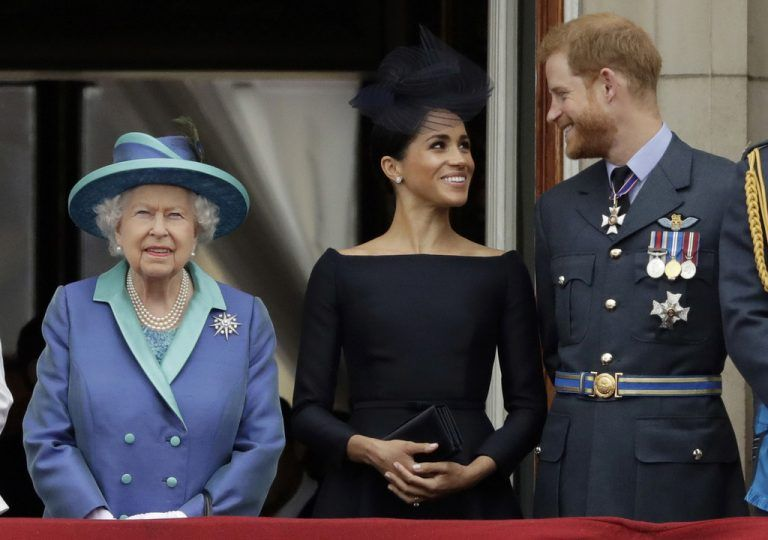 (FILES) In this file photo taken on July 10, 2018 (L-R) Britain's Queen Elizabeth II, Meghan, Duchess of Sussex, Britain's Prince Harry, Duke of Sussex stand on the balcony of Buckingham Palace in London to watch a military fly-past to mark the centenary of the Royal Air Force (RAF). - Britain's Queen Elizabeth II on January 13, 2020, said Prince Harry and his wife Meghan would be allowed to split their time between Britain and Canada while their future is finalised. The couple said last week they wanted to step back from the royal frontline, catching the family off guard and forcing the monarch to convene crisis talks about the pair's future roles. (Photo by Tolga AKMEN / AFP)