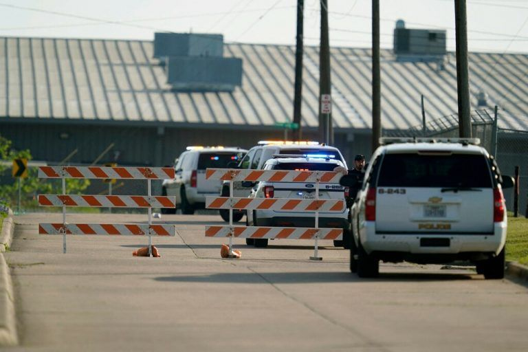 A Bryan police officer blocks access to an industrial park near the scene of a mass shooting in Bryan, Texas on April 8, 2021. - One person was dead and several in critical condition following a shooting at a business in Texas Thursday, just hours after US President Joe Biden called gun violence an